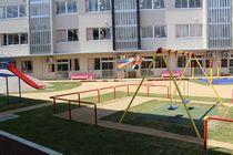 幼稚部園庭 左に赤い滑り台、右手前にブランコ、奥に広場、その向こうに校舎。
