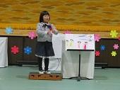 自分が描いた絵の横で話をする幼児。