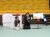 自分で作った絵の横で担任の先生と一緒に話をする幼児。