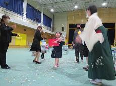 修了詔書と花束を抱え、紙吹雪が舞う中を歩く幼児。