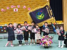 広げた校旗をバックに花束を抱えた修了児7名が並ぶ。
