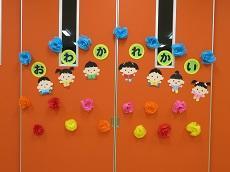 オレンジ色の壁に「おわかれかい」の文字、7人の子どものペープサート