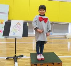 赤い蝶ネクタイをつけ、台の上に立つ司会の幼児。