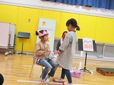 ピンク色の冠をかぶって椅子に座る幼児。その前にプレゼントを渡そうと立つ幼児。