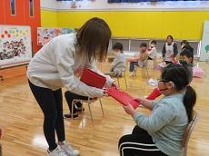 保護者代表が赤い包みのプレゼントを幼児に手渡す。