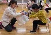 保護者代表が青い包みのプレゼントを幼児に渡す。頭を下げる幼児。
