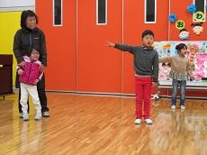 カレンダーの絵をバックに歌を歌う幼児3人。右手を横に伸ばして指を差している。
