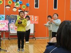カレンダーをバックに歌を歌う幼児4人。体の前で手を握って、友達の手話を表わす。