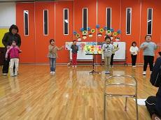 カレンダーをバックに、歌を歌う幼児7目人。両手を広げている。