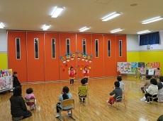 赤にピンクのフリルがついた衣装を着て、両手を上げて踊る幼児2人。椅子に座って見ている幼児の後ろ姿。