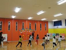 前に教員1名。両手を交互に上下に動かし、片足を後ろに蹴り上げて踊る子ども達。