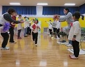 保護者、教員、在校児の作った花道を駆け抜ける幼児。