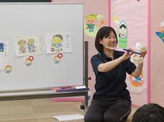 教員が見本の歯を持ち歯ブラシで磨きながら、歯磨きの仕方を指導している。
