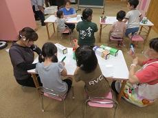 子ども達が机の上で透明の板にマジックで絵を描いている