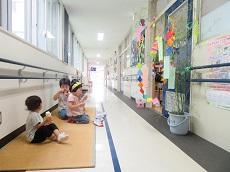 廊下に畳を敷き、子どもが3人七夕の飾りを付けた笹を前に座ってアイスクリームを食べている