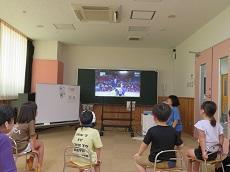 オリンピックの柔道の試合の様子を子ども達と教員が鑑賞している