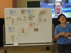 ホワイトボードにオリンピック競技のピクトグラムとそれぞれの競技のイラストを貼って説明している
