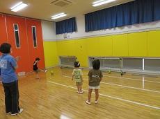 ボールをシュートする男児と応援する教員と女児2名