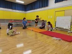 マットに向かって幅跳びしている男児と見守る教員と子ども達