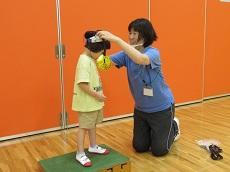 手作り金メダルを教員に首からかけてもらう女児