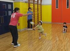 教員が持つ紐付きボールをバットで打つ女児