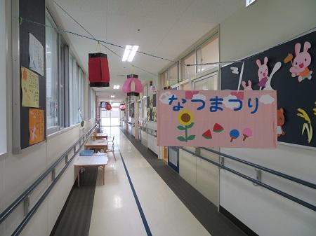 廊下に夏祭りと書いた看板と提灯が掛かっている
