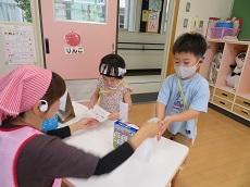 教員からアイスクリームを受け取る男児と女児